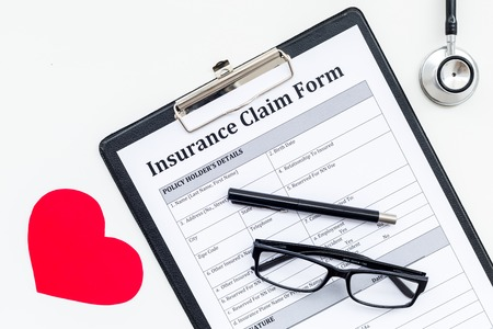 Health insurance claim form for fill out. Empty form near heart sign and stethoscope on white background top view. Stok Fotoğraf
