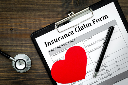 Health insurance claim form for fill out. Empty form near heart sign and stethoscope on dark wooden background top view.