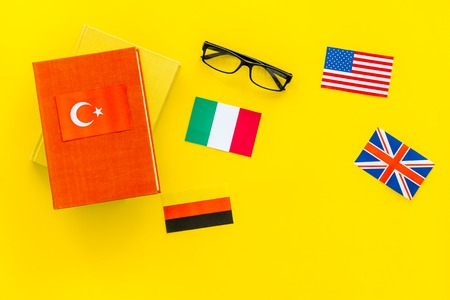 Language study concept. Textbooks or dictionaries of foreign language near flags on yellow backgrond top view.