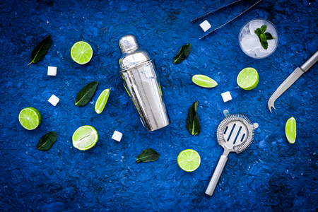 Ingredients and crockery for making mojito. Slices of lime, mint, sugar cubes, glass with ice cubes, shaker, strainer on blue background top view. Stock Photo
