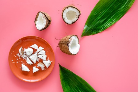 Pieces of coconut flesh on plate on pink background with coconut cut in half and palm leaves top view. Фото со стока
