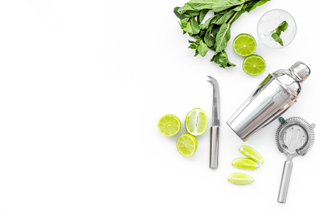 Process of making mojito concept. Ingredients and crockery. Slices of lime, mint, glass with ice cubes, shaker, strainer on white background top view. Stock Photo