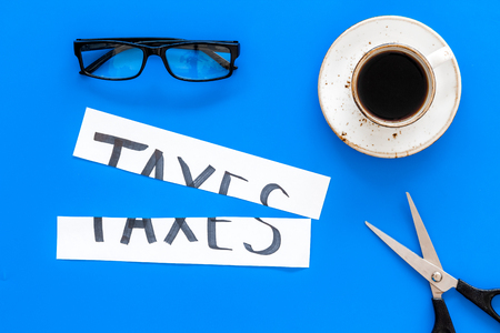 Tax reduce concept. Scissors and paper with word Taxes on blue background with coffee and glasses top view. Фото со стока