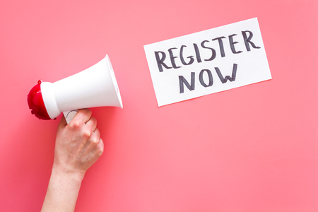 Register now hand lettering icon near megaphone on pink background top view. Stockfoto