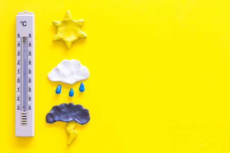 Weather forecast concept. Air temperature. Thermometer among cloud and lightening, sun, rainy clouds on yellow background top view. Stock Photo