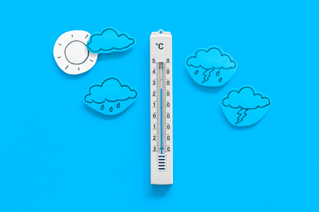 Weather forecast concept. Air temperature. Thermometer among cloud and lightening, sun, rainy clouds on blue background top view.