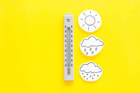 Weather forecast concept. Air temperature. Thermometer among cloud, sun, rainy clouds, snow on yellow and yellow background top view.