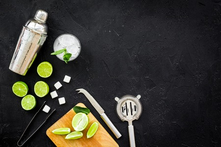 Make mojito cocktail with lime and mint. Shaker, strainer, glass near slices of lime on cutting board on black background top view copy space