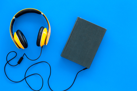 Audiobooks concept. Headphones connected with hardback book with empty cover on blue background top view copy space 版權商用圖片