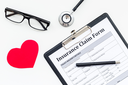 Health insurance claim form for fill out. Empty form near heart sign and stethoscope on white background top view Banco de Imagens - 102992918