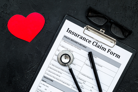 Health insurance claim form for fill out. Empty form near heart sign and stethoscope on black background top view