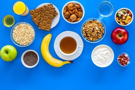 Make a menu for wholesome breakfast. Fruits, oatmeal, yogurt, nuts, crispbreads, chia on blue background top view copy space