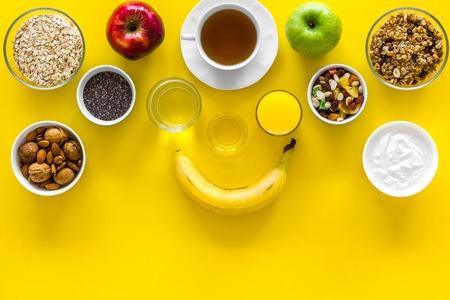 Ideas of healthy hearty breakfast for sportsmen. Fruits, oatmeal, yogurt, nuts, crispbreads, chia on yellow background top view copy space