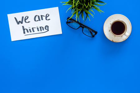 Search for worker, employee concept. We are hiring lettering on work desk on blue background top view copy space 写真素材