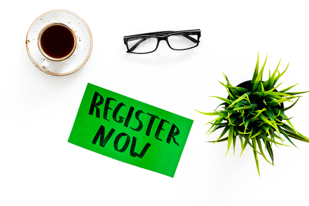 Membership concept. Register now hand lettering icon on word desk with glasses, coffee, plant on white background top view
