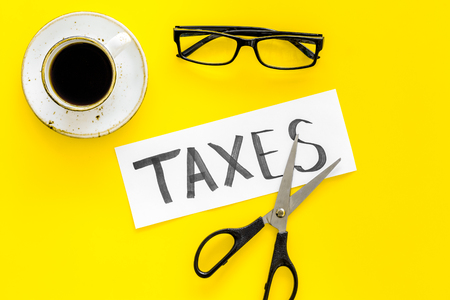 Tax reduce concept. Scissors and paper with word Taxes on yellow background with coffee and glasses top view Фото со стока