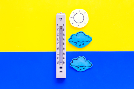 Weather forecast concept. Air temperature. Thermometer among cloud, sun, rainy clouds, snow on yellow and blue background top view copy space Stockfoto