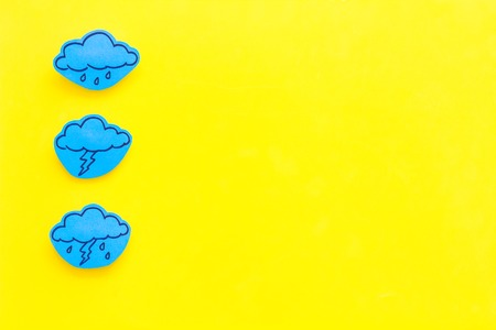 Rainfall forecast concept. Weather icons. Rainy cloud, lightening on yellow background top view copy space Imagens