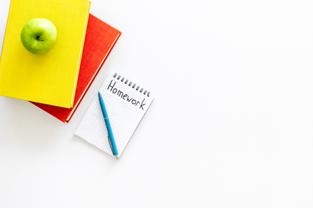 Homework concept. Word homework written in notebook on white desk with textbooks, tutorials and apple top view copy space