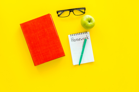 Homework concept. Word homework written in notebook on yellow desk with textbooks, tutorials and apple top view copy space Reklamní fotografie