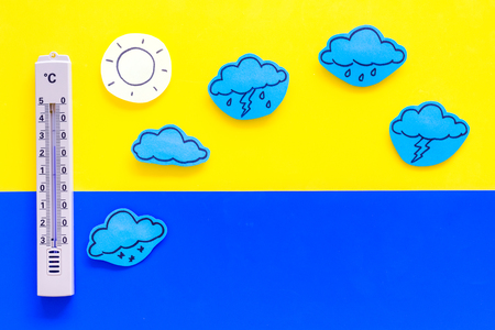Weather forecast concept. Air temperature. Thermometer among cloud and lightening, sun, rainy clouds on yellow and blue background top view copy space