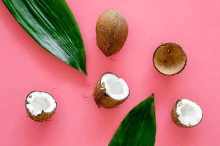 Tropical composition with coconut. Whole coconuts and coconut cut in half near palm leaves on pink background top view