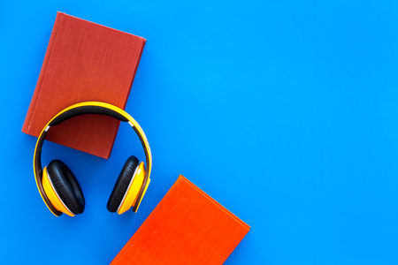 Distance education, e-learning concept. Headphones near hardback book with empty cover on blue background top view copy space 版權商用圖片