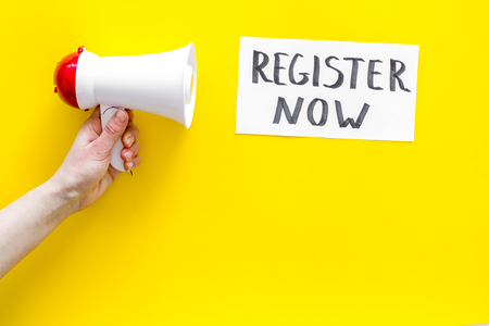 Register now hand lettering icon near megaphone on yellow background top view copy space
