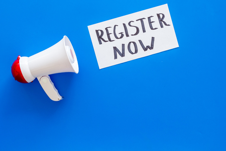 Register now hand lettering icon near megaphone on blue background top view copy space