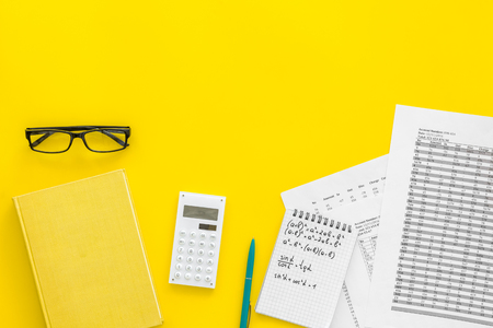 Math homework. Math textbook or tutorial near sheet with numbers, counts, calculator, notebook with formula on yellow background top view copy space