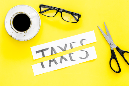 Tax reduce concept. Scissors and paper with word Taxes on yellow background with coffee and glasses top view 写真素材