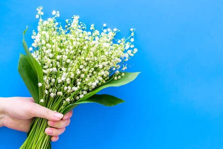 Give a bouquet of delicate lily of the valley flowers. Hand hold bunch of flowers on pastel blue background top view.