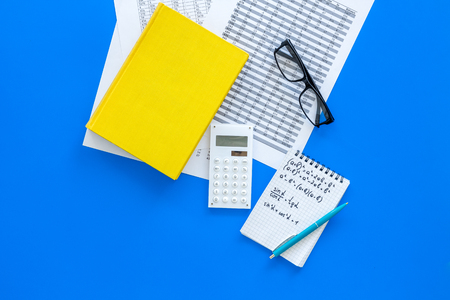 Math homework. Math textbook or tutorial near sheet with numbers, counts, calculator, notebook with formula on blue background top view.