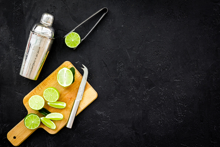 Process of making mojito concept. Ingredients and crockery. Slices of lime, mint, shaker, tongs on black background top view.