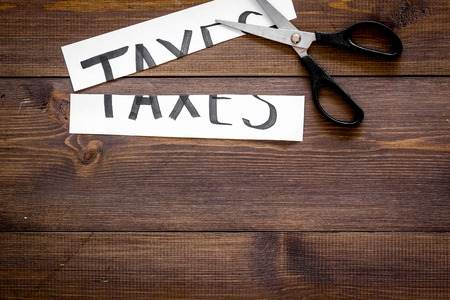 Cut taxes concept. Scissors cut paper with word Taxes on dark wooden background top view. 写真素材