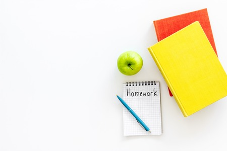 Homework concept. Word homework written in notebook on white desk with textbooks and tutorials top view. Stock Photo