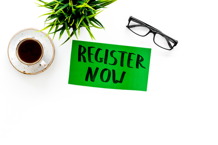 Membership concept. Template for registration. Register now hand lettering icon on word desk with glasses, coffee, plant on white background top view.