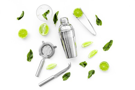 Process of making mojito concept. Ingredients and crockery. Slices of lime, mint, glass with ice cubes, shaker, strainer on white background top view. 스톡 콘텐츠