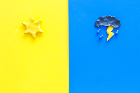 Good and bad weather concept. Template for forecast. Sun vs cloud and lightening on yellow and blue background top view.
