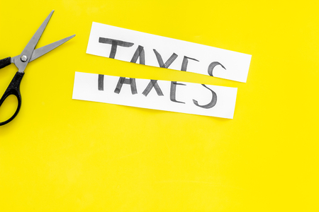 Cut taxes concept. Scissors cut paper with word Taxes on yellow background top view. 写真素材