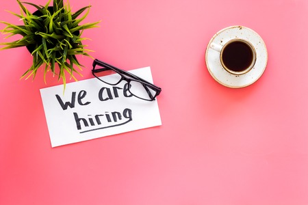 Search for worker, employee concept. We are hiring lettering on work desk on pink background top view. Stock Photo