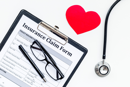 Health insurance claim form for fill out. Empty form near heart sign and stethoscope on white background top view. Stock Photo