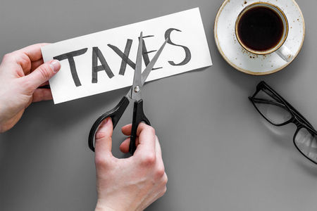Tax reduce concept. Hands with scissors cut paper with word Taxes on grey background top view