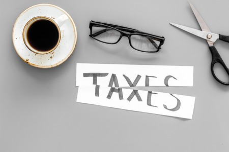Tax reduce concept. Scissors and paper with word Taxes on grey background with coffee and glasses top view Фото со стока