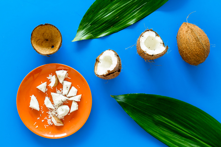 Pieces of coconut flesh on plate on blue background with coconut cut in half and palm leaves top view