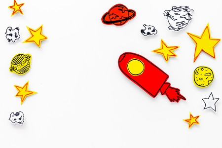 Space tourism concept. Drawn rocket or spaceship near stars, planets, asteroids on white background top view copy space