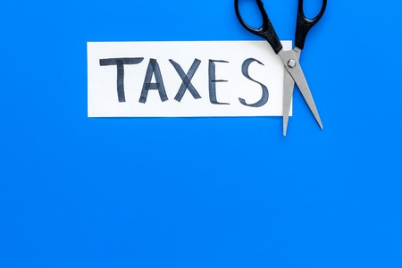 Cut taxes concept. Scissors cut paper with word Taxes on blue background top view space for text