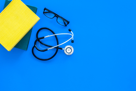 Medical education concept. Stethoscope near textbook of medicine and glasses on blue background top view copy space