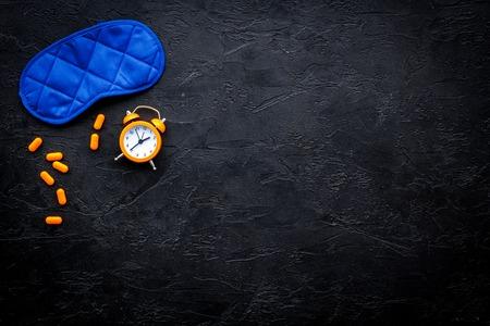 Medicine helps get asleep. Good sleep. Sleeping pills near sleeping mask and alarm clock on black background top view copy space 版權商用圖片