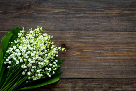 May flowers. Bouquet of lily of the valley flowers on dark wooden background top view copy space